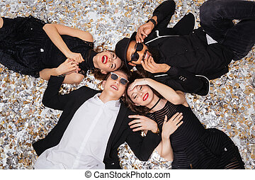 Joyful young people smiling and lying on sparkling confetti...