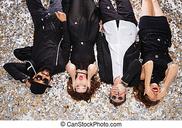 Funny friends grimacing and lying on sparkling confetti -...