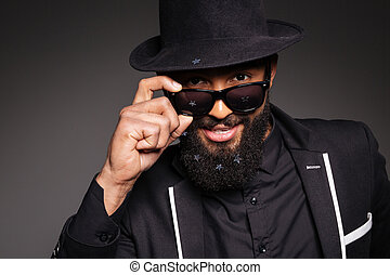 Stylish afro american man looking at camera over black...