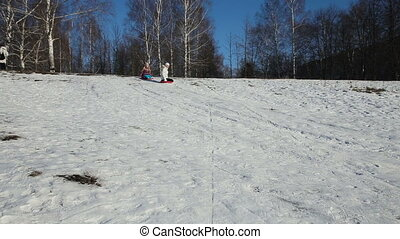 Yong girls sledging down hill - Girls sledging down hill,...