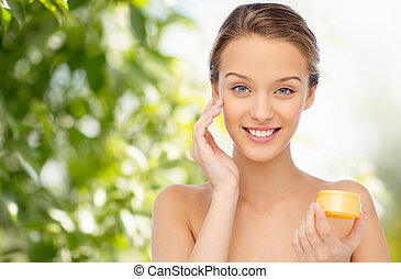 happy young woman applying cream to her face - beauty,...