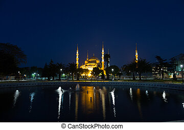 Sultan Ahmed Mosque with reflection in water at night,...
