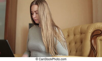 Closeup of a beautiful young woman with a laptop , working at home. Beautiful female model.