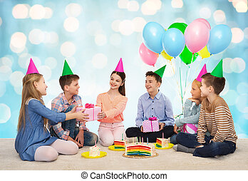 happy children giving presents at birthday party