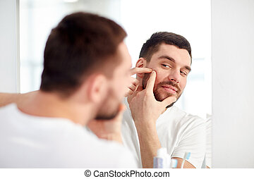 man squeezing pimple at bathroom mirror - beauty, hygiene,...
