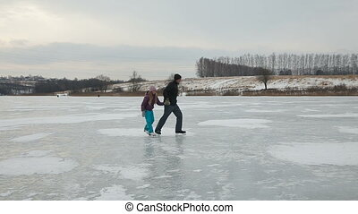 Father with daughter ice skating on frozen lake