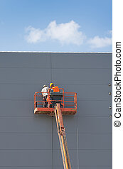 Workers in lifting cage - Construction workers installing...