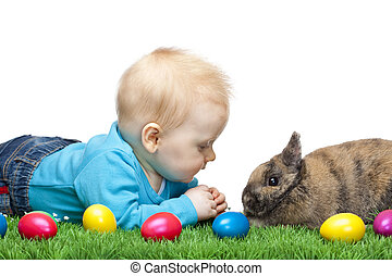 Baby is sitting in meadow together with Easter bunny and colorful eggs. Isolated on white Background.