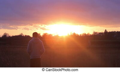 man standing and looking at the sunset