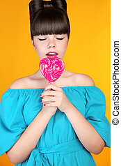 Lollypop candy Beautiful teen girl eating colourful Heart...