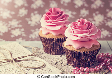 Cupcakes with sweet rose flowers and a letter