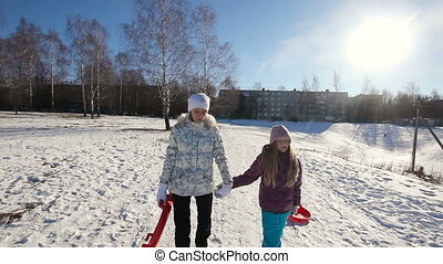 Girls with sled walking in the park - Young girls with...