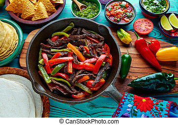 Beef fajitas in a pan sauces chili and sides Mexican - Beef...