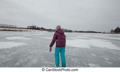 Young girl ice skating on frozen lake