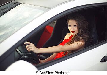 Beautiful smiling girl driver driving in car, sensual...