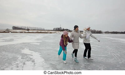 Family ice skating on frozen lake - Mother with daughters...