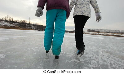Family ice skating on frozen lake - Ice skates closeup.Happy...