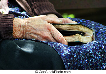 Elder hands holding the Holy Bible - RAMETI, ROMANIA - JUNE...