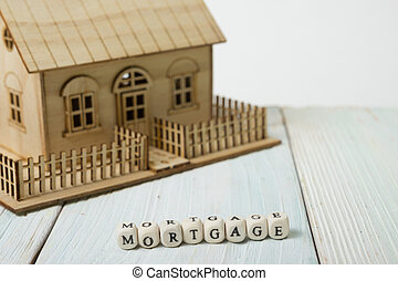 Wooden blocks spelling the word Mortgage on wood table
