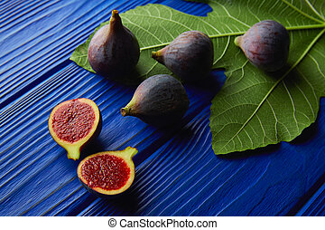 figs raw cutted fruits and fig tree leaves on blue wooden...