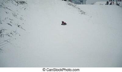 Yong girls sledging down hill - Girls sledding down a hill...