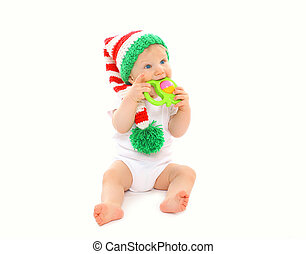 Baby in knitted hat playing with toy on white background