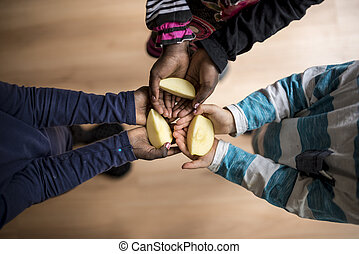 Three kids of mixed races each holding a piece of apple in...
