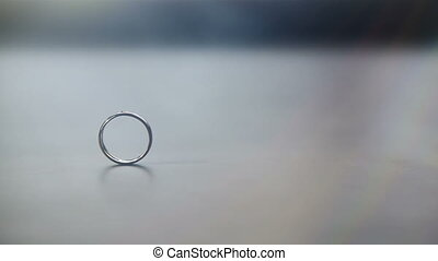 Two wedding rings - Wedding ring rolling on the table and...