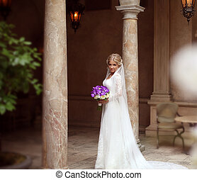 Beautiful Bride Portrait in wedding dress, attractive young woman with bouquet of flowers between marble column