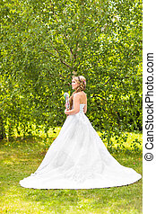 Beauty bride in bridal gown with bouquet and lace veil on...