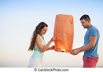 Couple start a red Chinese sky lantern in the dusk near the...