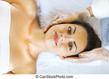 Close up portrait of a young woman getting spa treatment