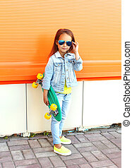 Beautiful little girl child with skateboard in city