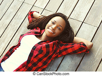 Beautiful smiling young african woman relaxed on wooden...