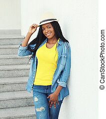 Fashion beautiful smiling african woman wearing a straw hat and jeans clothes in city