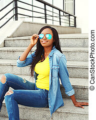 Fashion beautiful smiling african woman wearing a sunglasses and jeans clothes in city