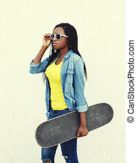 Fashion pretty african woman with skateboard in jeans clothes and sunglasses, profile view