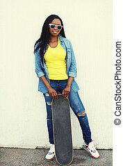 Fashion pretty young african woman with skateboard in colorful jeans clothes and sunglasses