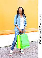 Beautiful smiling african woman with shopping bags in city over colorful orange background