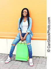 Beautiful young smiling african woman with shopping bags in city over colorful orange background