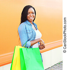Portrait beautiful smiling african woman with shopping bags in city over colorful orange background
