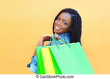 Portrait beautiful smiling african woman with shopping bags in city over orange background