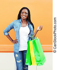 Portrait beautiful smiling young african woman with shopping bags in city over colorful orange background