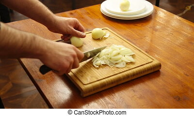 The hands cutting onions on a chopping board fast