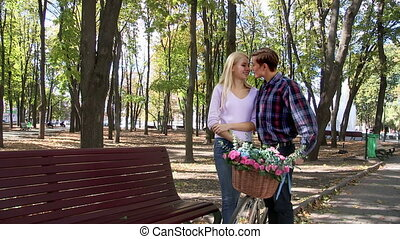 Couple with retro bike kissing in the park. - Kissing young...