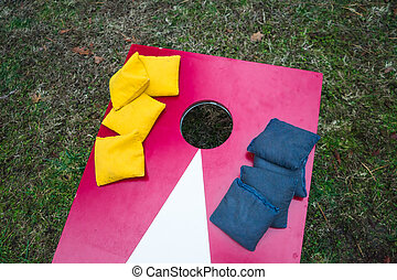 Stacked Bean Bags on Cornhole Board - Bean bags stacked on...