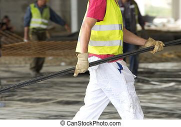 Worker carrying armature - Construction worker carrying...