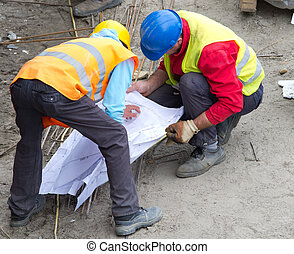 Construction workers reading plan