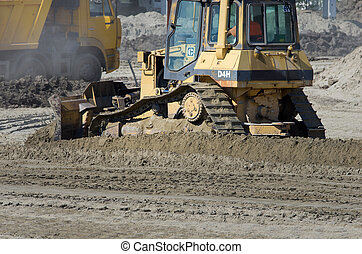 Bulldozer caterpillar working on sand ground at construction...