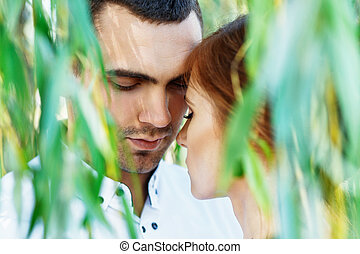 Young casual couple enjoy of each other under tree